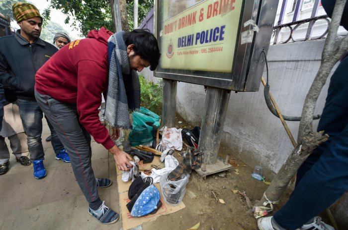 A member of an NGO watches articles of violent protesters and broken police batton sticks after a rally against the Citizenship Amendment Act (CAA). PTI