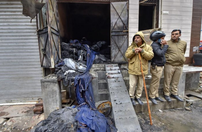 Policemen stand outside the damaged three-storey residential-cum-commercial building where a fire broke out, in outer Delhi's Kirari area. (PTI photo)