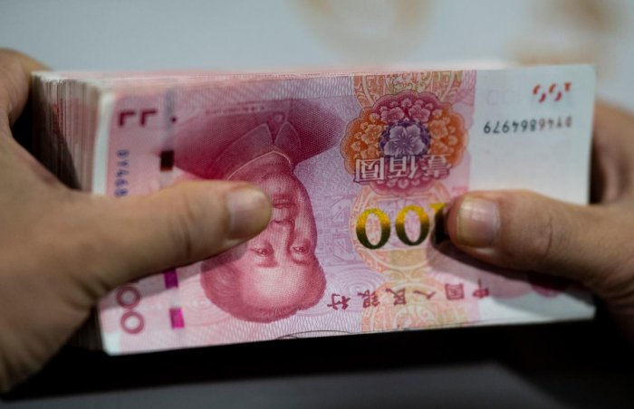 A bank employee counting out 100 yuan (14.6 USD) notes at a bank in Shanghai. (AFP Photo)