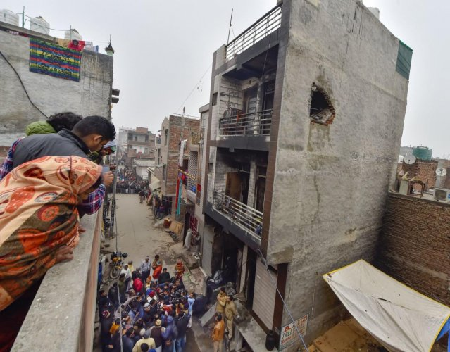 Neighbours look at the damaged three-storey residential-cum-commercial building where a fire broke out, in outer Delhi's Kirari area, Monday, Dec. 23, 2019. At least nine people, including three children, were killed in the incident. (PTI Photo)
