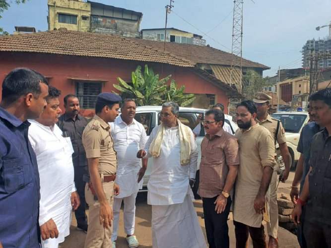 Former chief minister Siddaramaiah collects information from police on firing, near Bunder Police Station, in Mangaluru on Monday.
