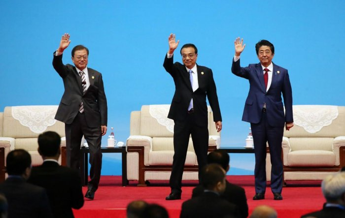South Korea's President Moon Jae-in, Chinese Premier Li Keqiang and Japanese Prime Minister Shinzo Abe wave at the beginning of the trilateral business meeting between China, South Korea and Japan in Chengdu, southwestern China's Sichuan province on December 24, 2019. (AFP Photo)