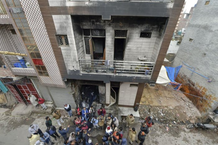 Police and media persons stand outside a three-storey residential-cum-commercial building where a fire broke out, in outer Delhi's Kirari area, Monday, Dec. 23, 2019. At least nine people, including three children, were killed in the incident. (PTI Photo)