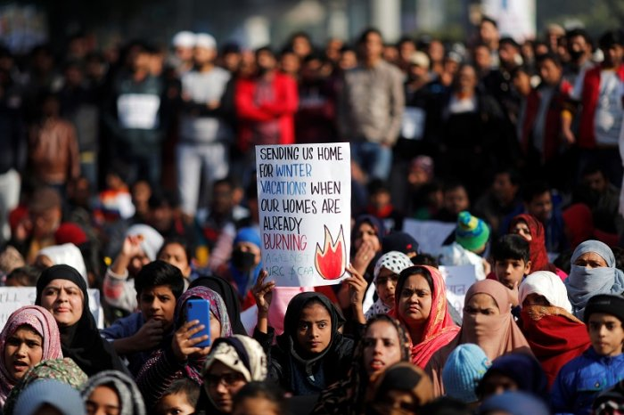 A girl holds a placard as she attends a protest against a new citizenship law, outside the Jamia Millia Islamia university in New Delhi. (Reuters Photo)