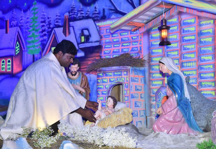 Fr Sudeep placing Infant Jesus in the crib at Infant Jesus Church in Bengaluru on Christmas eve on Tuesday. DH PHOTO/Janardhan B K
