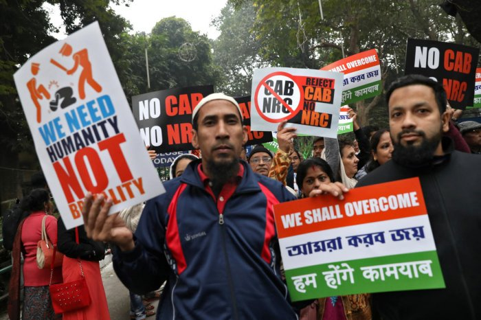 Demonstrators display placards during a silent rally to protest against a new citizenship law, in Kolkata. Reuters