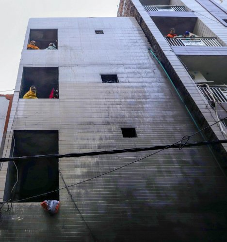 People watch from a house in Krishna Nagar which engulfed in a fire during wee hours of Thursday, Dec 26, 2019