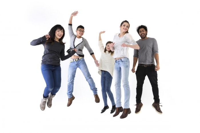 Happy group of five friends jumping.