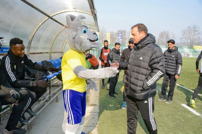 Real Kashmir FC Head Coach David Robertson shakes hands with the mascot during a practice session ahead of their I-League 2019-20 match with Chennai City FC, in Srinagar, Wednesday, Dec. 25, 2019. Kashmir is all set to host first National level football match post-abrogration of Article 370 and bifurcation of the State. (PTI Photo)