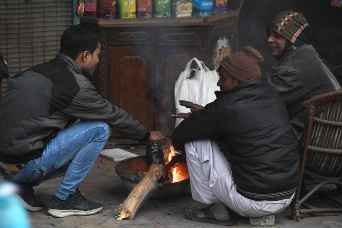 People warm themselves around fire as temperature in Delhi dips two notches below normal. (AFP Photo)