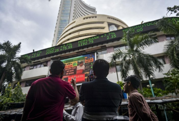 Bystanders react as they watch the stock prices displayed on a digital screen outside BSE building, in Mumbai. (PTI Photo)