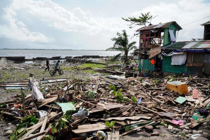 Residents walk past a house damaged during Typhoon Phanfone in Tacloban, Leyte province in the central Philippines on December 25, 2019. (AFP Photo)