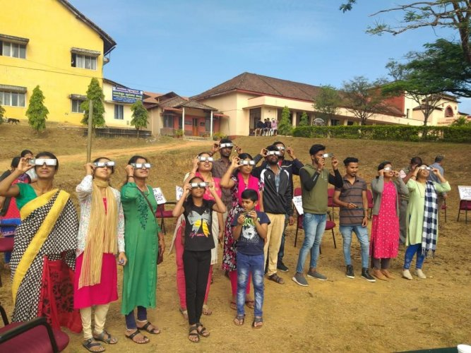Students and alumni of Field Marshal K M Cariappa College, Madikeri, watch the solareclipse on Thursday.