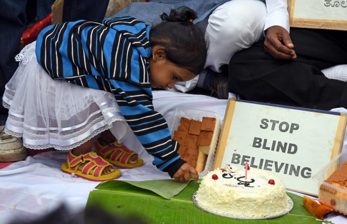 A young girl cuts a cake during an event organised to dispel myths about the eclipse on Thursday. DH photo/Pushkar V