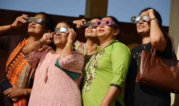 People watch solar eclipse using special glasses at General Thimmayya Circle in Madikeri on Thursday. DH Photo