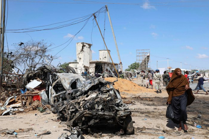 A Somali woman walks past a wreckage at the scene of a car bomb explosion at a checkpoint in Mogadishu. Photo/Reuters