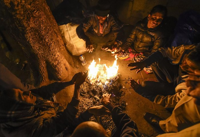 Workers warm themselves at a bonfire on a cold winter in in New Delhi. PTI