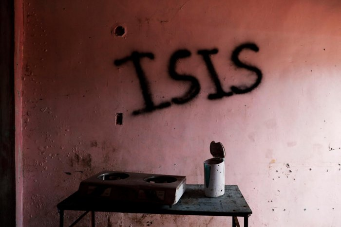 "Burnt kitchen items are seen in front of a wall spray-painted with the word ""ISIS"" in a home in the most affected war-torn area of Marawi City. (Reuters Photo)"