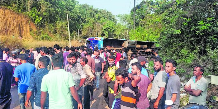 People gather around the private bus, which hit a car before falling into a roadside culvert, on the outskirts of Mangaluru on Saturday.