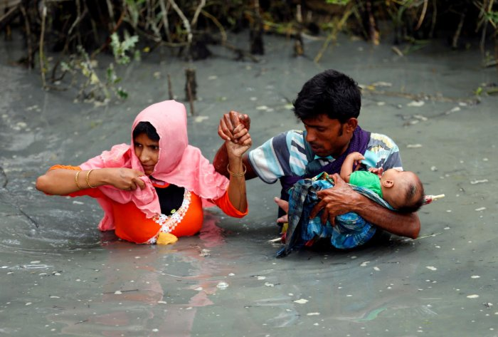 Rohingya refugees carry their child as they walk through water after crossing border by boat through the Naf River in Teknaf, Bangladesh. Photo/Reuters