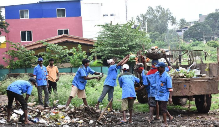 Civic workers cleaning the street in Hubballi-Dharwad City.