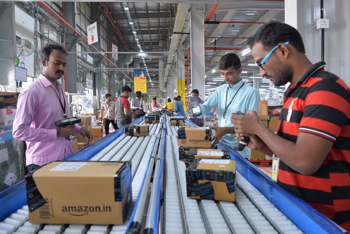 Employees of Amazon scan packages at an Amazon's newly launched Fulfilment Centres (FCs) situated in the suburban area of Bangalore on September 18, 2018. (AFP Photo)