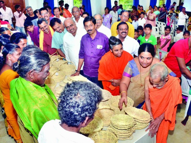 Pejawar seer inspects the baskets made by members of Koraga community. DH File Photo