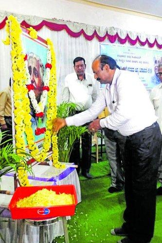 District Kannada Sahitya Parishat President B S Lokesh Sagar pays floral tributes to a portrait of Kuvempu on the occasion of Rastrakavi Kuvempu birth anniversary at D Devraj Urs Bhavana in Madikeri on Sunday.