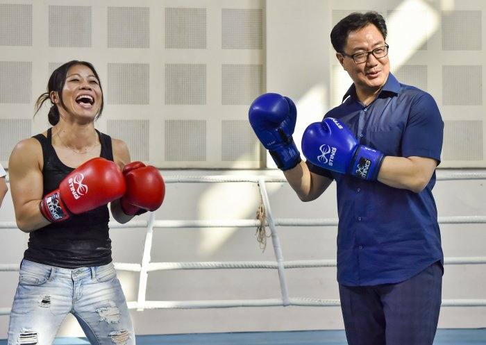 Sports Minister Kiren Rijiju wearing boxing gloves poses with World Champion boxer Mary Kom for photographs at Indira Gandhi Stadium in New Delhi. (PTI Photo)