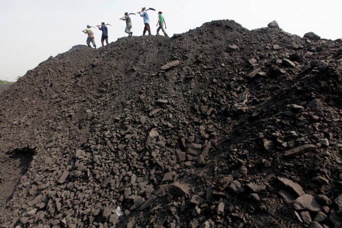 Workers walk on a heap of coal at a stockyard of an underground coal mine in the Mahanadi coal fields at Dera, near Talcher town in the eastern Indian state of Orissa March 28, 2012. (Reuters Photo)