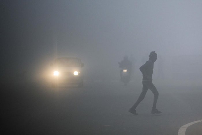 A man crosses a street as commuters make their way under heavy foggy conditions in New Delhi on December 30, 2019. (AFP Photo)