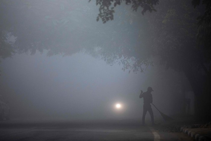 A man sweeps a street under heavy foggy conditions in New Delhi. (AFP Photo)