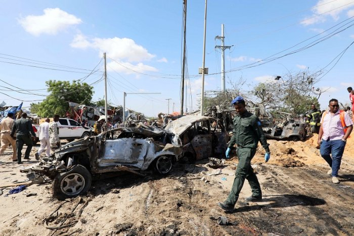 A Somali police officer walks past a wreckage at the scene of a car bomb explosion at a checkpoint in Mogadishu, Somalia. (Reuters Photo)