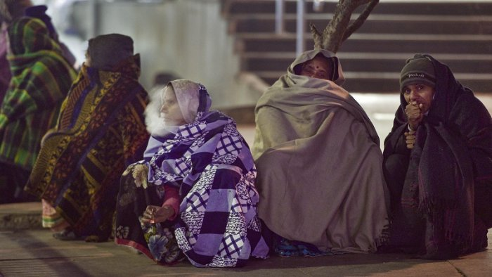 People wear warm clothes to protect themselves on a cold winter evening outside AIIMS in New Delhi. (PTI Photo)