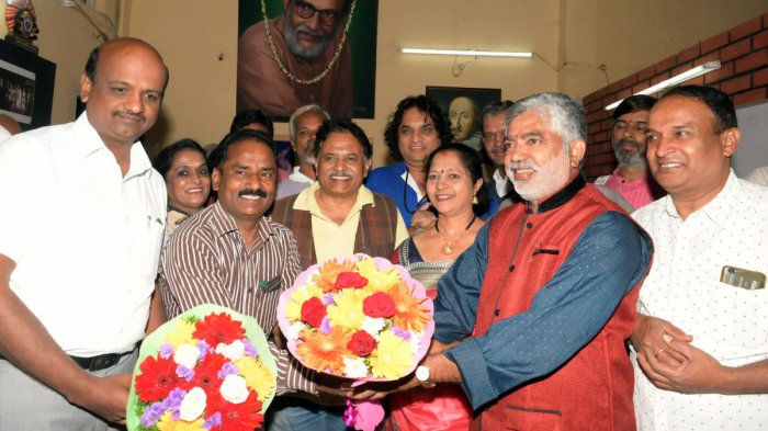Rangayana Joint Director V N Mallikarjuna Swamy welcomes new Director Addanda Cariappa in Mysuru, on Tuesday. Kannada and Culture Assistant Director H Chennappa, and theatre person Anitha Cariappa are seen. dh photo