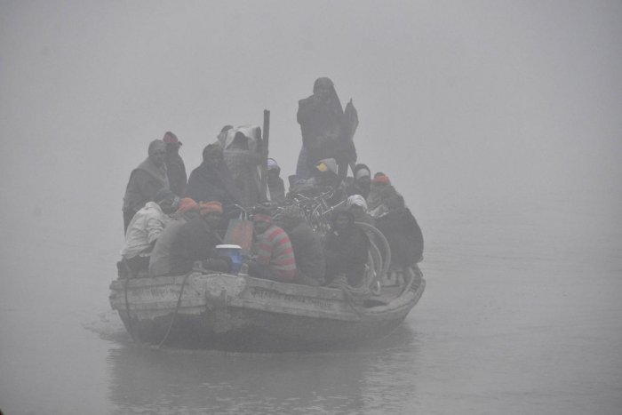 A boat overloaded with passengers and bicycles crosses the River Ganga on a cold and foggy morning in Patna