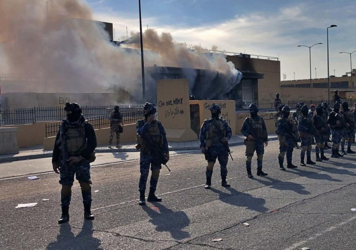 Iraqi security forces stand guard as smoke rises from the U.S. embassy compound in Baghdad, Iraq, Wednesday, Jan. 1, 2020. AP