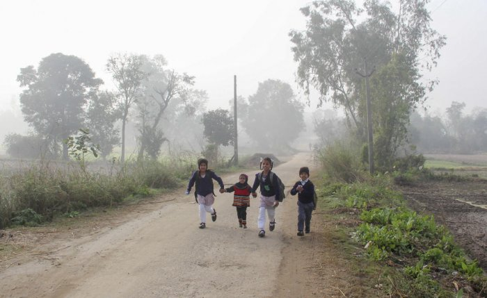 Children on their way to school during a cold and foggy morning, on the outskirts of Jammu, Monday, Dec. 16, 2019. (PTI Photo)