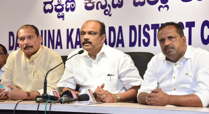 DCC President K Harish Kumar (centre) addresses reporters in Mangaluru on Tuesday.