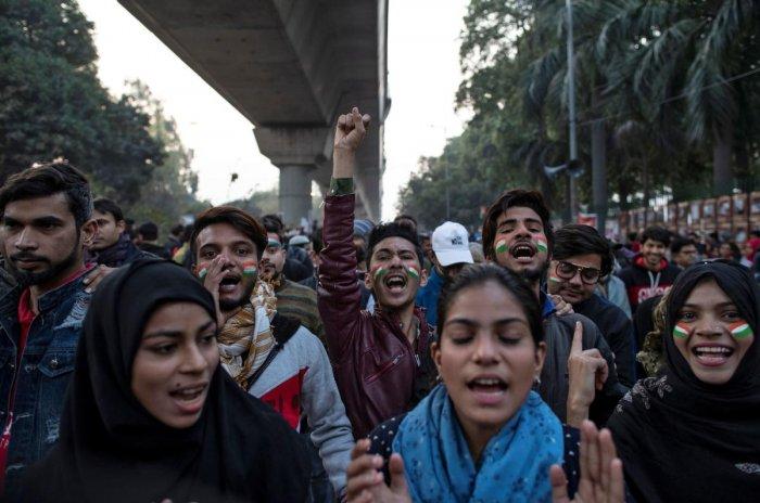 Demonstrators attend a protest against a new citizenship law, outside the Jamia Millia Islamia university in New Delhi