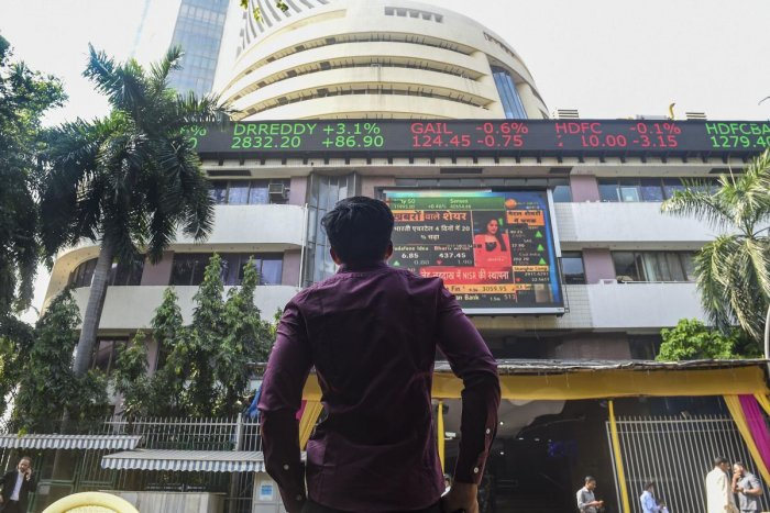 A bystander watches the stock prices displayed on a digital screen at the facade of the Bombay Stock Exchange (BSE) building, in Mumbai, Wednesday, Nov. 20, 2019. Sensex reached an all-time high at more than 40800 points. (PTI Photo)