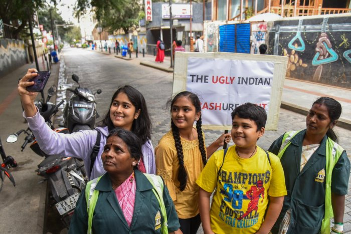 Civic volunteers and pourakarmikas pose on a clean Church Street on Wednesday. DH PHOTO