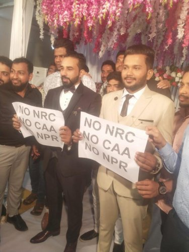Bridegrooms Mohammed Rilwan and U S Nihal hold posters opposing NRC and CAA at Unity Hall at Kallapu on the outskirts of Mangaluru.