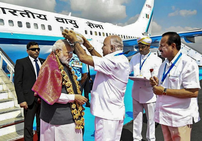 Prime Minister Narendra Modi being greeted by Karnataka Chief Minister BS Yediyurappa, as Union Minister for chemicals and fertilizers Sadananda Gowda looks on, upon his arrival at a airport in Bengaluru, Thursday, Jan. 2, 2020. Modi is on a 2-day visit to Bengaluru. (PTI Photo)