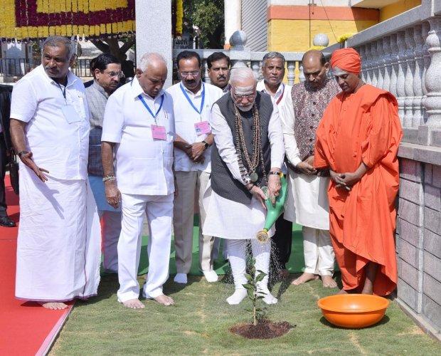 Prime Minister Narendra Modi plants a sapling of Bilva Patre plant on the premises of Shivakumara Swamiji's Gadduge at Siddaganga Mutt in Tumakuru on Thursday. Siddalinga Swamy, Chief Minister B S Yediyurappa, Union ministers Pralhad Joshi, Sadananda Gowd