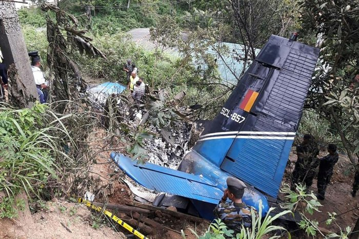 Rescue workers inspect the wreckage of a Sri Lankan air force plane that crashed in Haputale on January 3, 2020. - A Sri Lankan air force plane crashed in a tea-growing mountainous region on January 3, killing the four crew on board, a military official said. (Photo by STR / AFP)