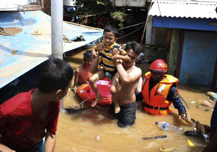 Rescuers evacuate a boy from his house in flooded neighborhood in Jakarta. (Photo credit: AP)