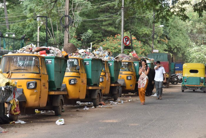 Pedestrians cover their nose and walks near lined up garbage filled BBMP tippers on bazar street at Halasuru in Bengaluru on Wednesday 03rd October 2018. Photo by Janardhan B K