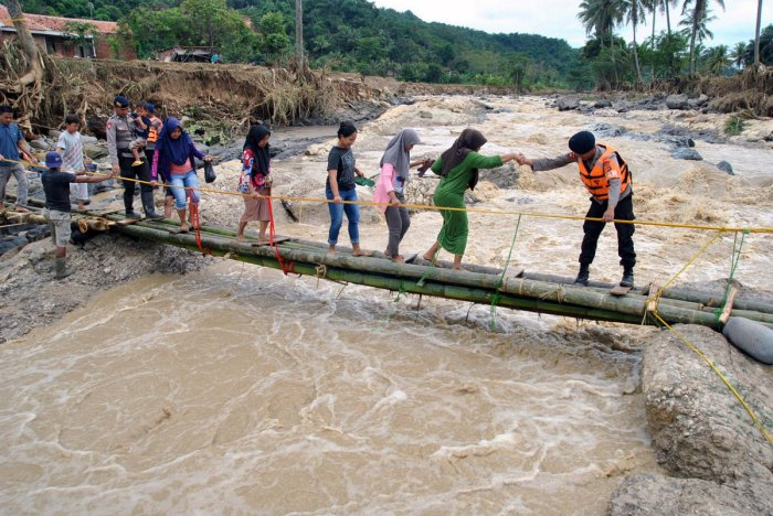 Police officers help people to get through an emergency bridge over the Cidurian river in Bogor, Indonesia, January 3, 2020. (Reuters Photo)