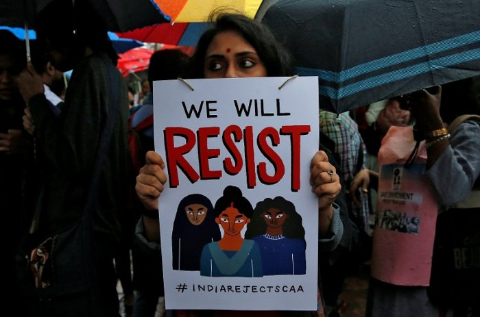 A demonstrator displays a placard as she attends a protest rally against a new citizenship law, in Kolkata. (Reuters Photo)